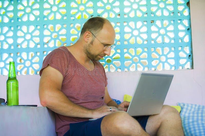 Homem feliz e seguro novo do mochileiro que trabalha com o laptop relaxado fora como o empresário autônomo e o nômadas digital imagem de stock