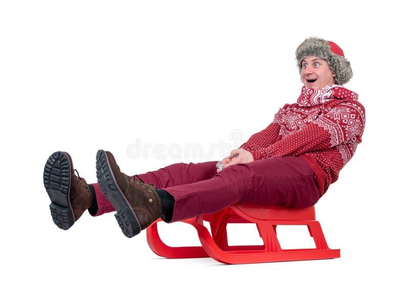 Homem feliz em passeios de uma camiseta vermelha, do lenço e do chapéu um trenó, isolado no fundo branco fotografia de stock