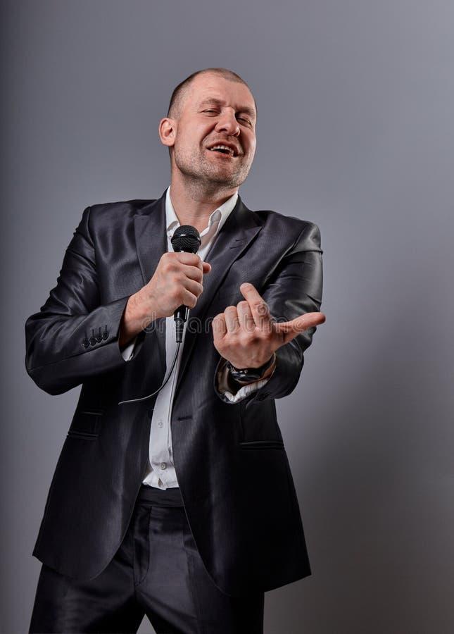 Homem feliz emocional de sorriso do executor que apresenta o microfone da terra arrendada da mostra na m?o e em convidar o dedo n foto de stock