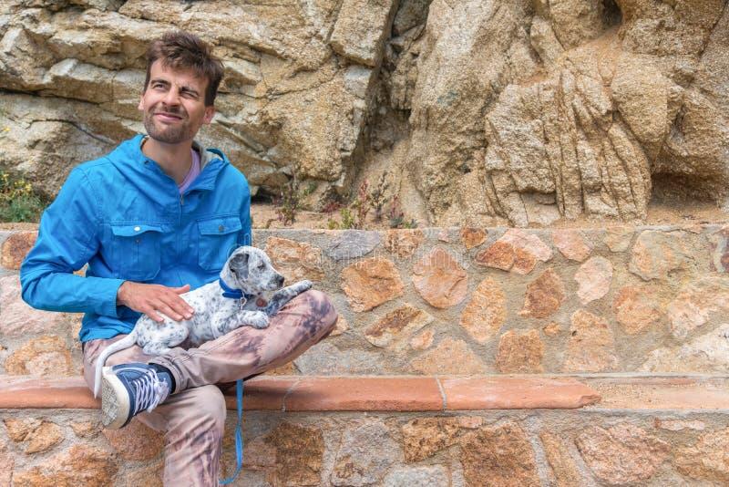 Homem feliz feliz guardando seu cachorrinho Dalmatian misturado adotado e sentando-se no banco de pedra Pets o conceito da ado??o foto de stock royalty free