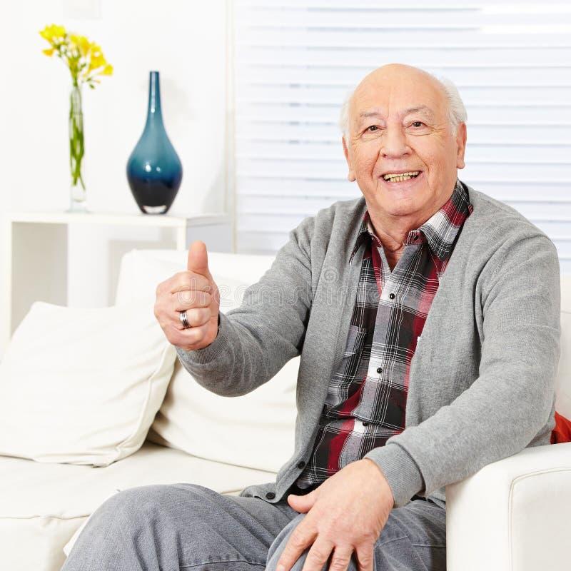Homem feliz idoso que mantém os polegares fotografia de stock