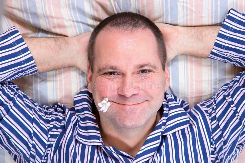 Homem feliz na cama fotos de stock royalty free