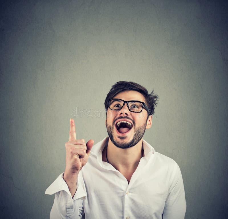 homem feliz na camisa e nos vidros brancos que aponta acima no fundo cinzento imagem de stock royalty free