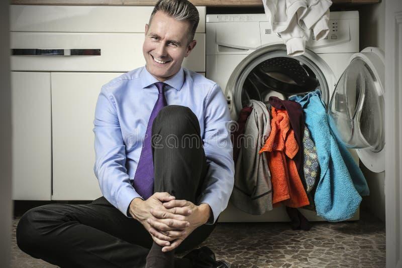 Homem feliz na lavandaria imagem de stock royalty free