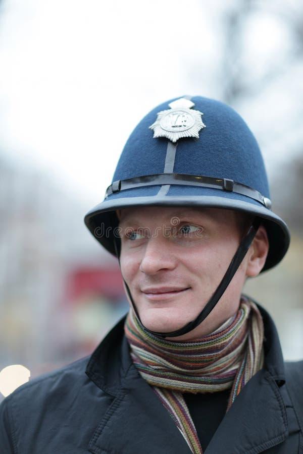 Homem feliz no chapéu britânico da polícia imagem de stock royalty free