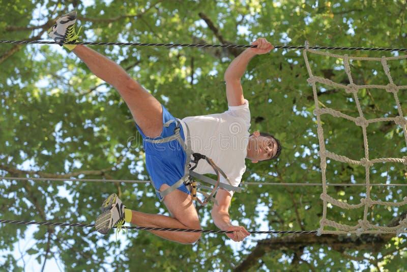 Homem feliz no parque extremo da corda com carabiners imagens de stock