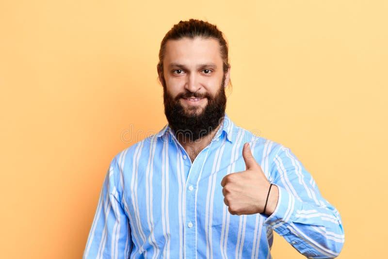 Homem feliz no polegar à moda da exibição da camisa acima imagens de stock royalty free