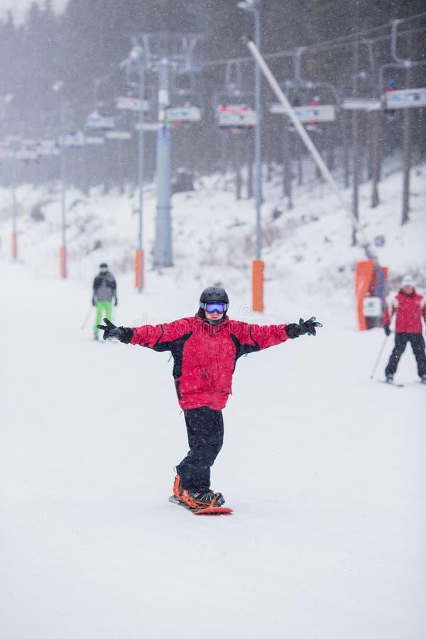 Homem feliz no revestimento vermelho no skiin do snowboard para baixo na montanha Está nevando imagem de stock royalty free
