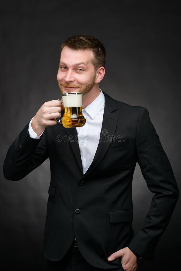 Homem feliz no terno preto que guarda a caneca de cerveja imagens de stock royalty free