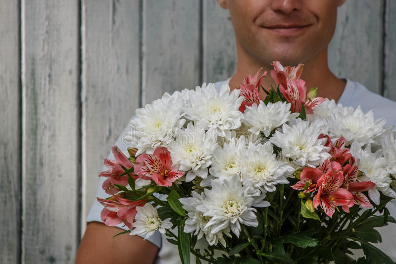 Homem feliz novo com as flores brancas no fundo de madeira fotos de stock royalty free