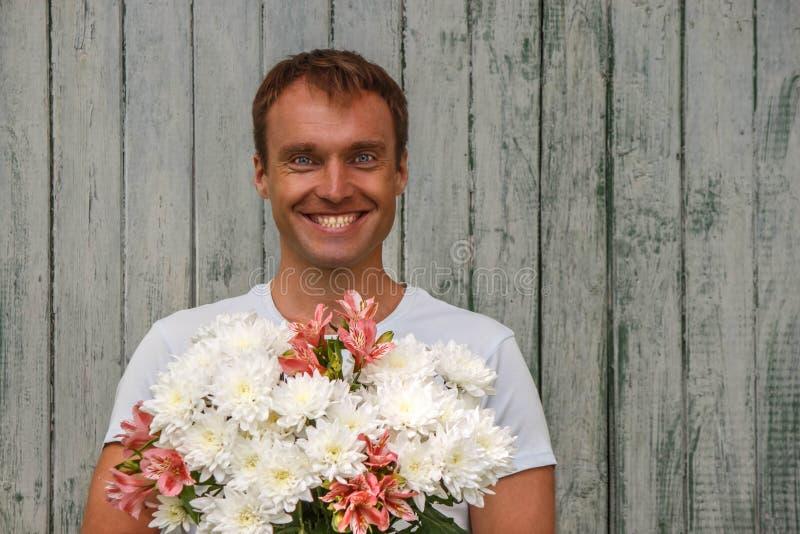 Homem feliz novo com as flores brancas no fundo de madeira foto de stock royalty free