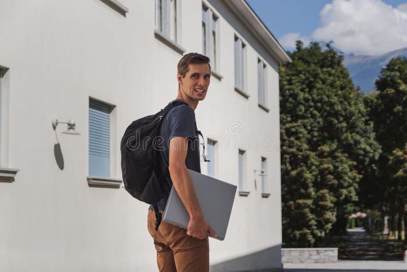 Homem feliz novo com trouxa que anda à escola após férias de verão fotos de stock