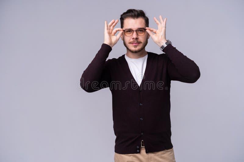 Homem feliz novo nos monóculos que levantam seguramente com sorriso grande no fundo cinzento foto de stock royalty free