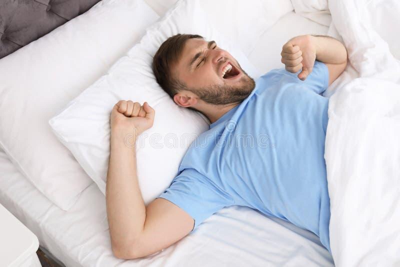 Homem feliz novo que acorda após o sono fotografia de stock royalty free