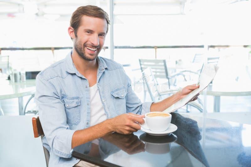Homem feliz novo que guarda os jornais ao olhar a câmera imagens de stock royalty free