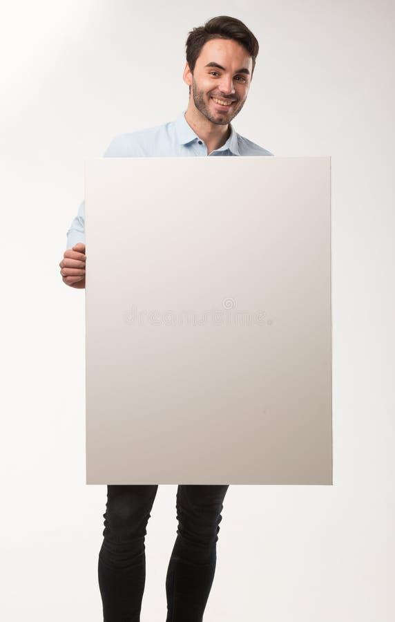 Homem feliz novo que mostra a apresentação, apontando no cartaz sobre o fundo cinzento fotos de stock