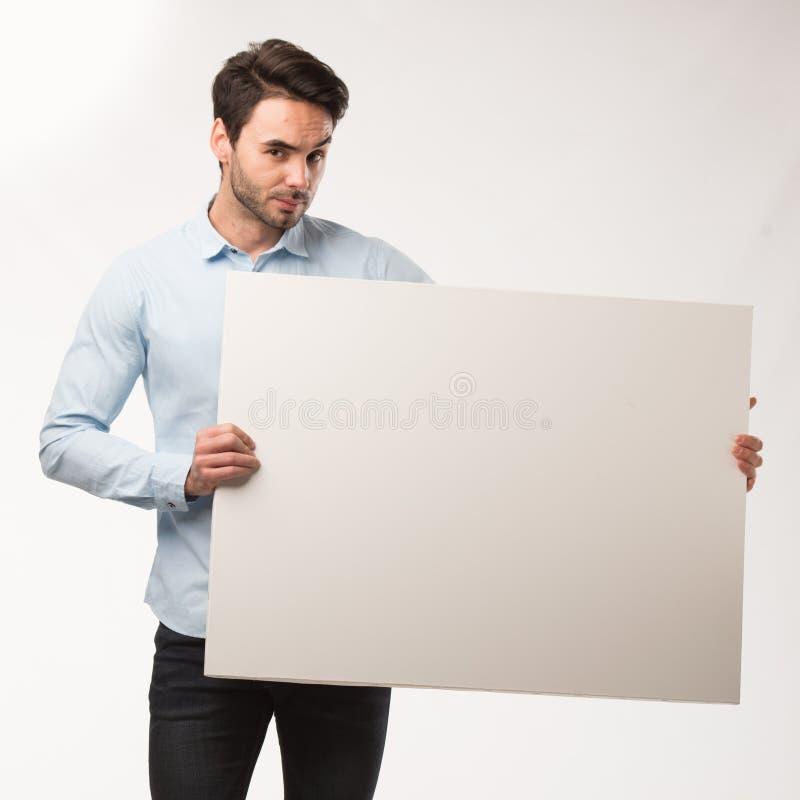 Homem feliz novo que mostra a apresentação, apontando no cartaz sobre o fundo cinzento imagens de stock