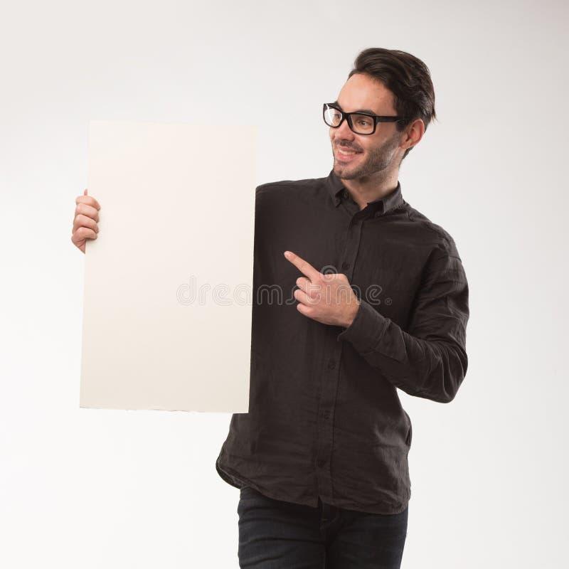 Homem feliz novo que mostra a apresentação, apontando no cartaz sobre o fundo cinzento fotografia de stock royalty free