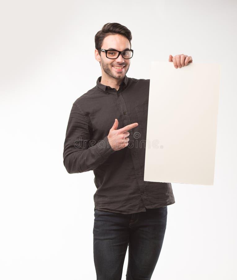 Homem feliz novo que mostra a apresentação, apontando no cartaz sobre o fundo cinzento foto de stock