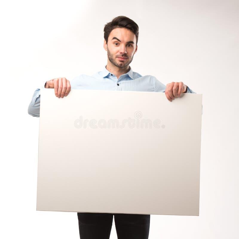 Homem feliz novo que mostra a apresentação, apontando no cartaz sobre o fundo cinzento imagem de stock royalty free