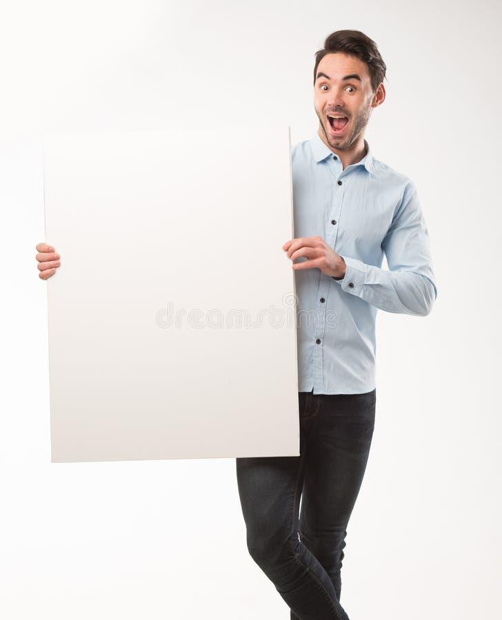 Homem feliz novo que mostra a apresentação, apontando no cartaz sobre o fundo cinzento imagens de stock royalty free