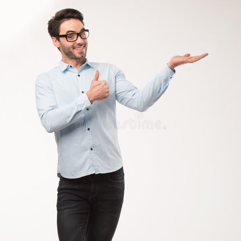Homem feliz novo que mostra a apresentação, apontando no cartaz sobre o fundo cinzento fotos de stock royalty free