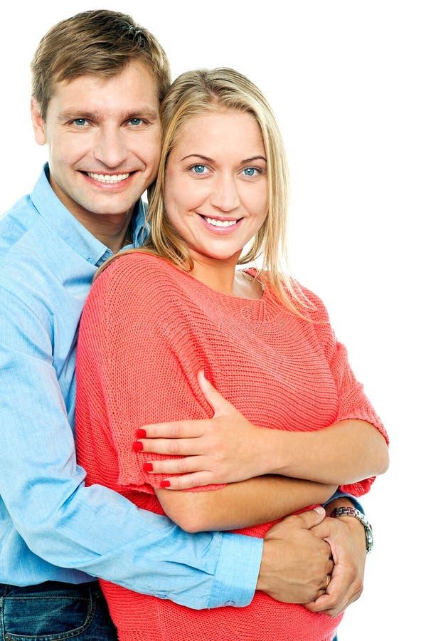 Homem feliz que abraça sua esposa de atrás fotografia de stock royalty free