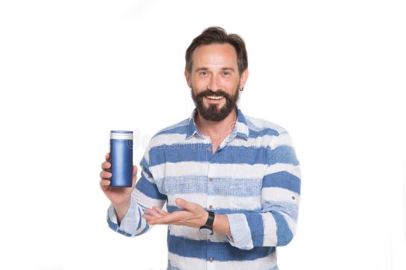 Homem feliz que aponta à garrafa do champô e do sorriso fotos de stock royalty free
