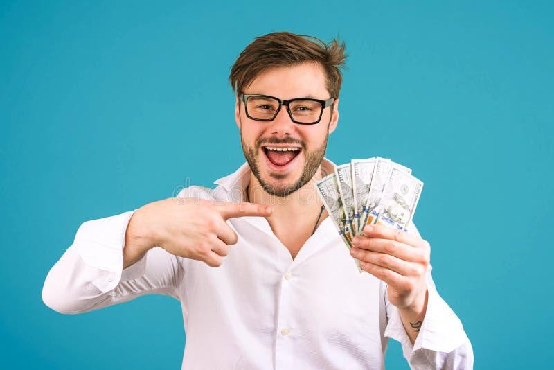 Homem feliz que aponta na pilha dos dólares fotografia de stock royalty free