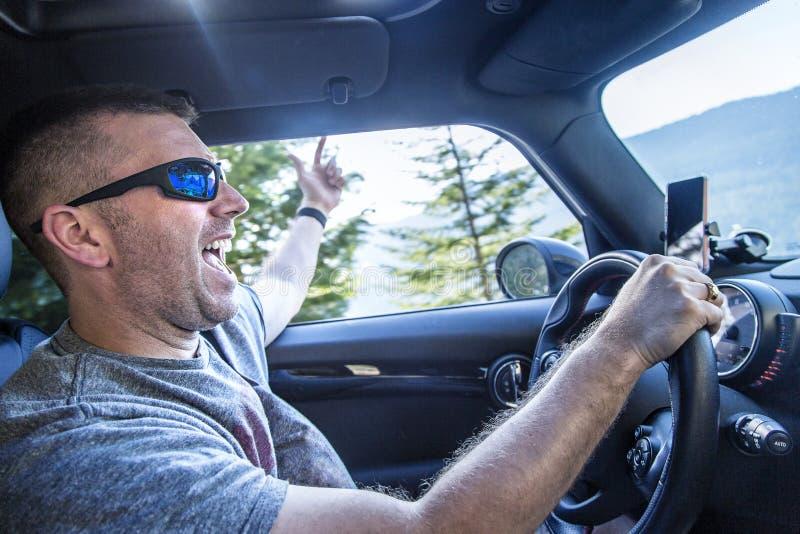 Homem feliz que aprecia uma viagem por estrada em seu carro em um dia ensolarado fotografia de stock royalty free