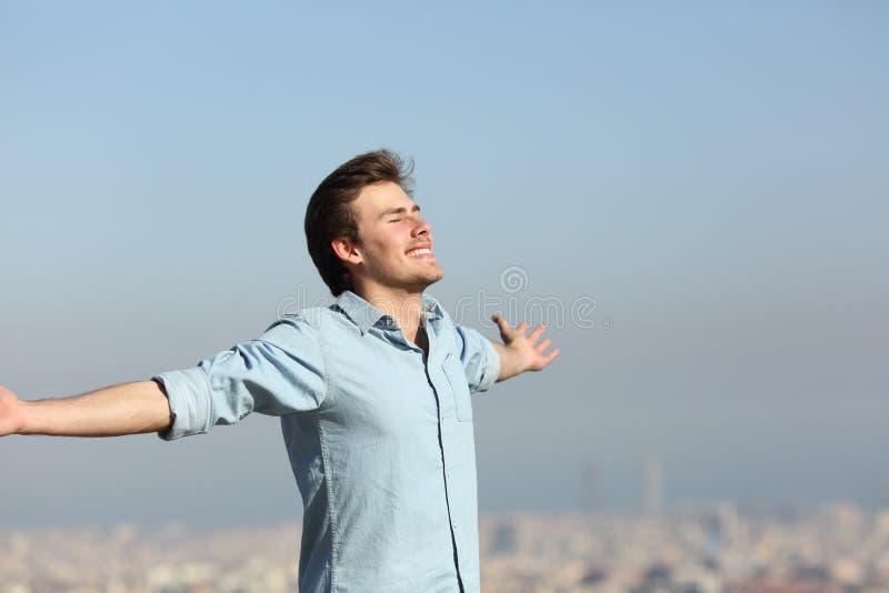 Homem feliz que comemora o dia novo com fundo urbano imagem de stock