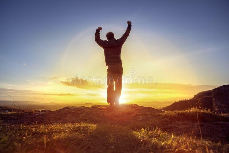 Homem feliz que comemora o sucesso de vencimento contra o por do sol imagens de stock royalty free