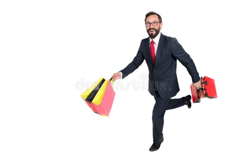 Homem feliz que corre com os sacos de papel contra o fundo branco imagem de stock