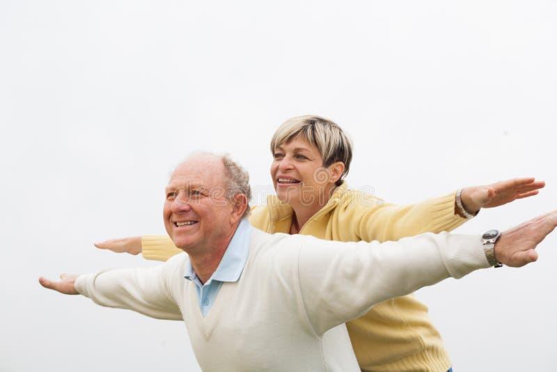 Homem feliz que dá às cavalitas à mulher foto de stock