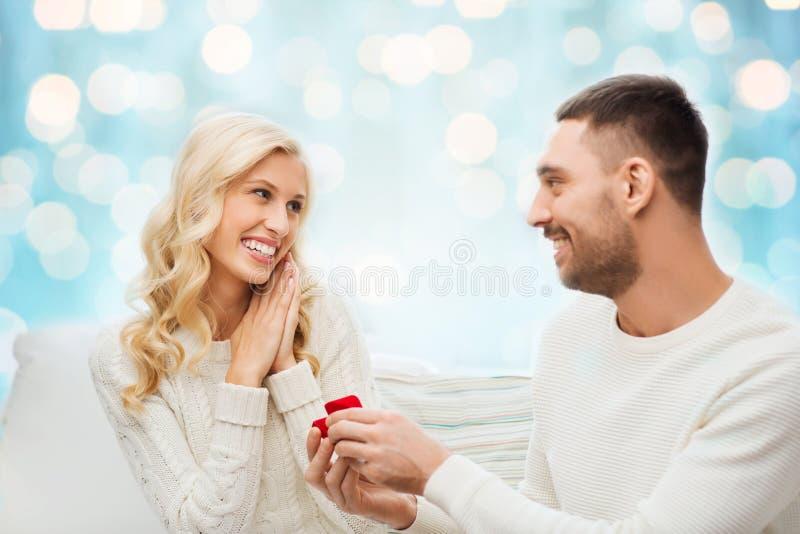 Homem feliz que dá o anel de noivado à mulher imagem de stock