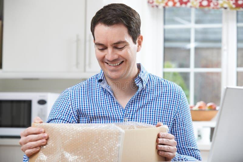 Homem feliz que desembala a compra em linha em casa fotografia de stock royalty free