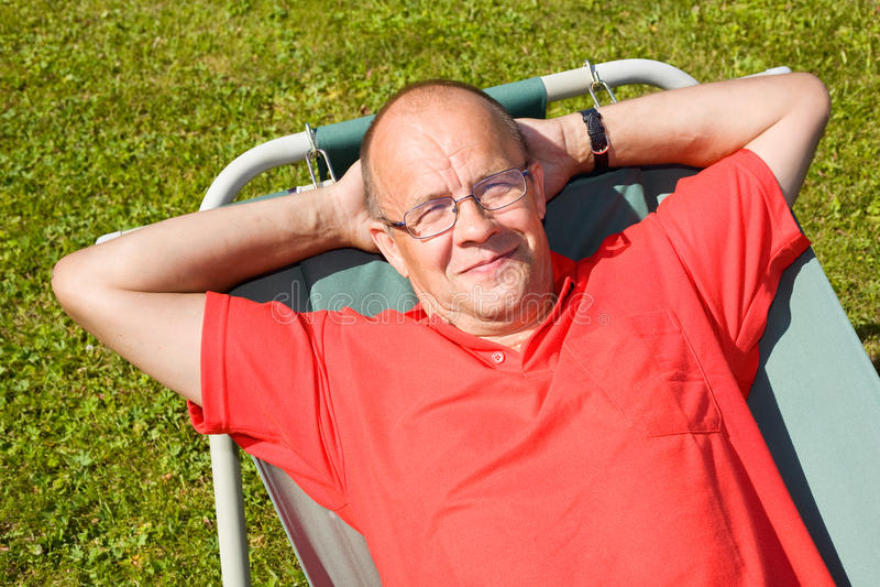 Homem feliz que encontra-se no hammock fotografia de stock