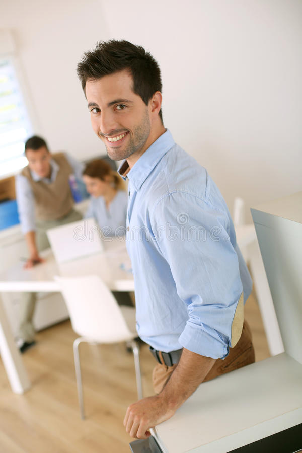Homem feliz que está no escritório foto de stock royalty free