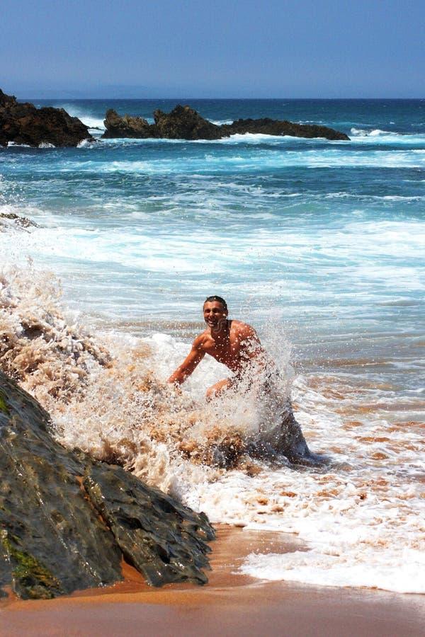 Homem feliz que está sendo espirrado por uma onda na praia foto de stock