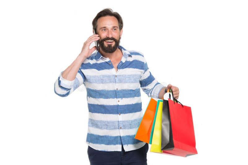 Homem feliz que fala no telefone ao estar com compras imagens de stock