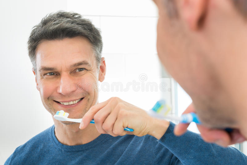 Homem feliz que guarda a escova de dentes foto de stock royalty free