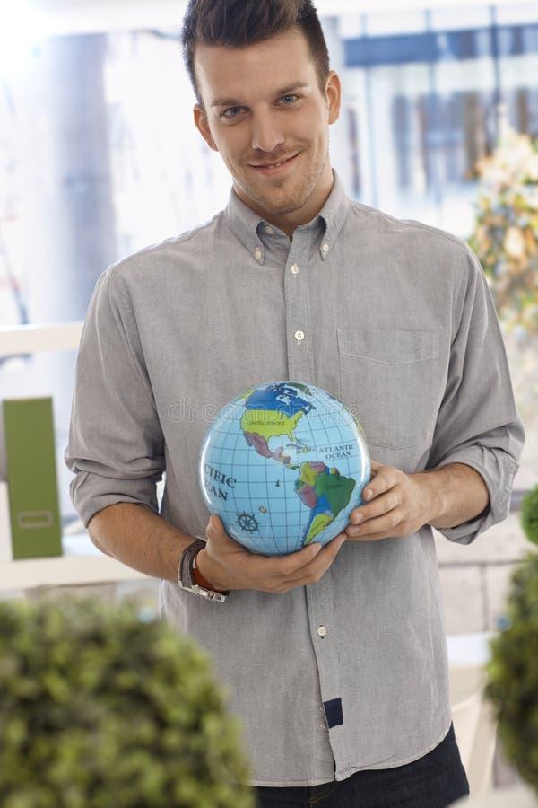 Homem feliz que guarda o globo pequeno imagens de stock royalty free