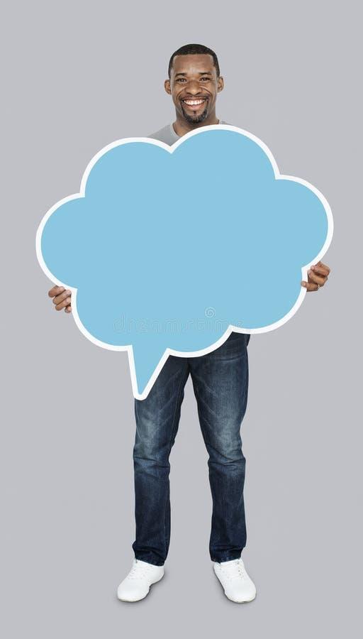 Homem feliz que guarda um ícone da bolha do discurso imagens de stock