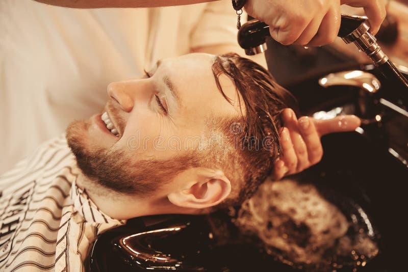 Homem feliz que lava sua cabeça no dissipador especial do cabeleireiro com o entalhe para o pescoço Barbearia imagem de stock royalty free