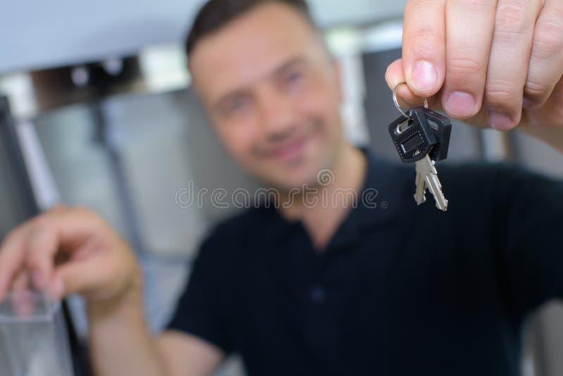 Homem feliz que mostra chaves à casa nova fotografia de stock