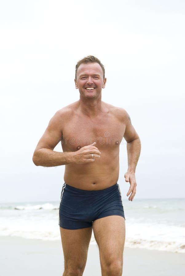 Homem feliz que movimenta-se na praia. fotografia de stock