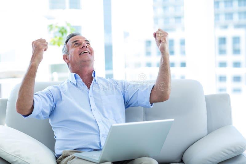 Homem feliz que olha acima ao trabalhar no portátil foto de stock royalty free