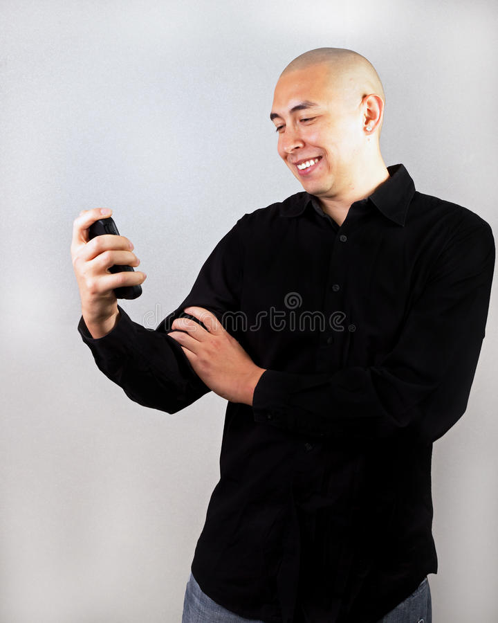 Homem feliz que olha seu Smartphone foto de stock