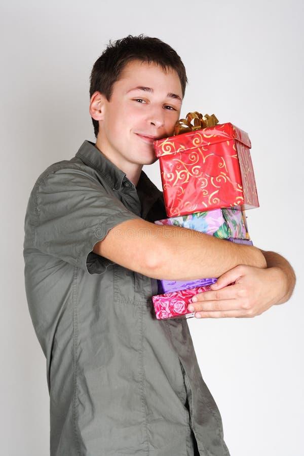 Homem feliz que prende muitos presentes e sorriso imagem de stock royalty free