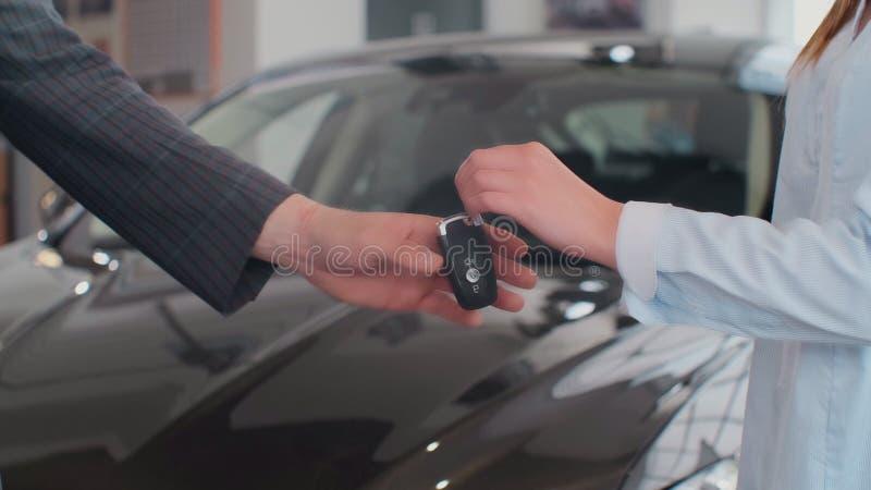 Homem feliz que recebe chaves a seu carro comprado novo com o concession?rio autom?vel profissional no neg?cio das vendas dos car imagens de stock royalty free